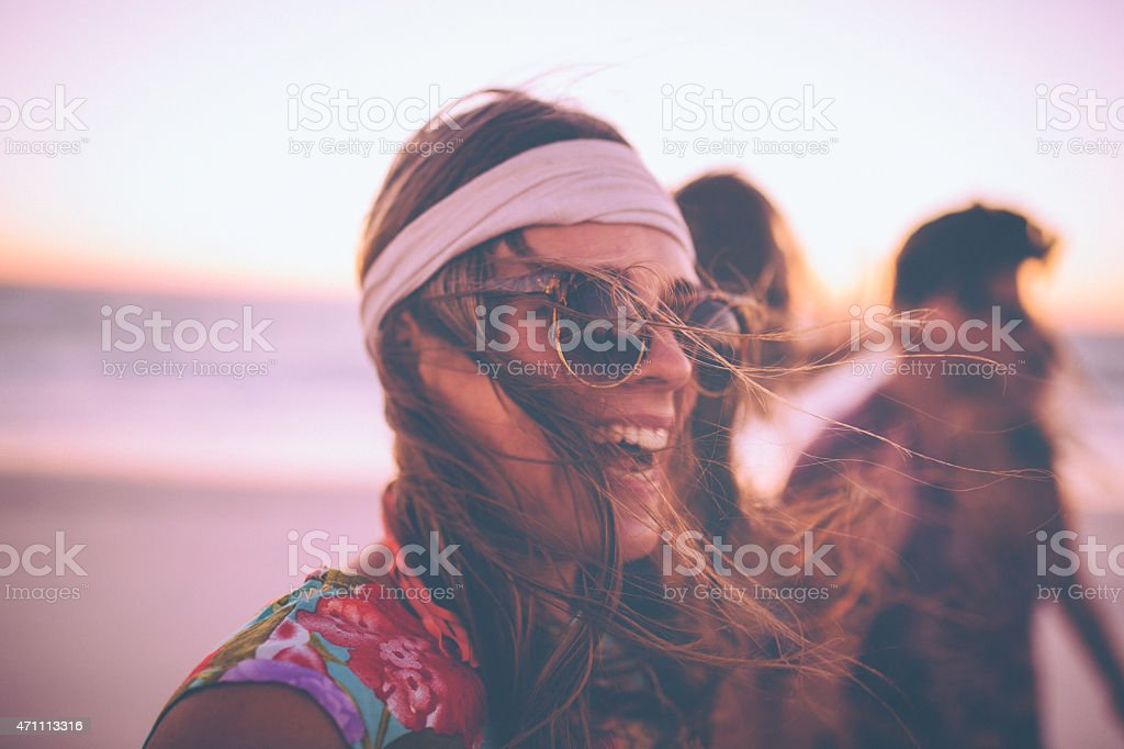 Boho Girl in sunglasses laughing on a beach with friends stock photo