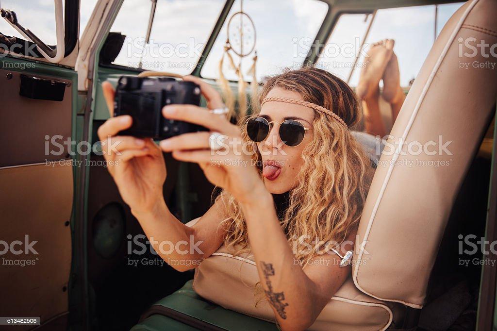 Boho girl in vintage van taking road trip selfie stock photo