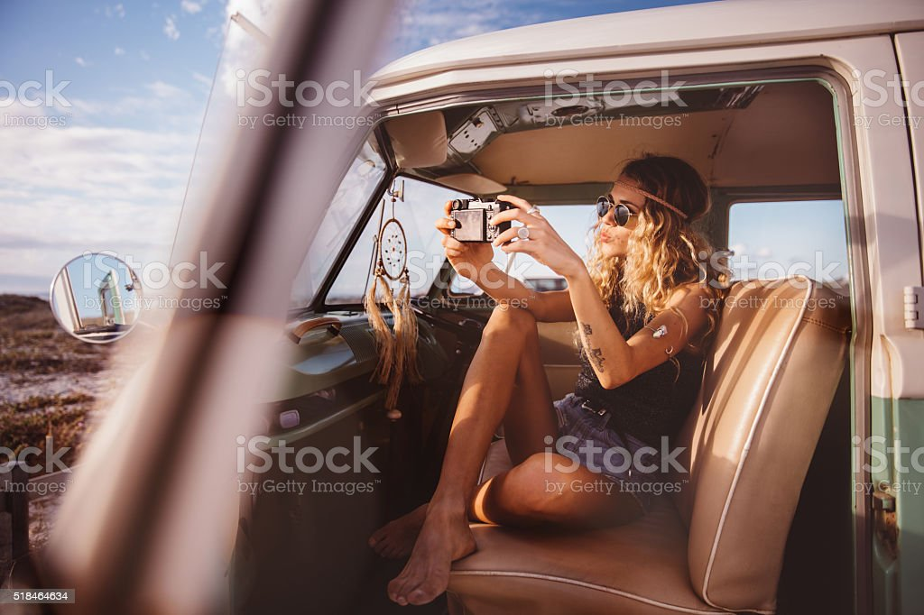 Boho girl in vintage van taking road trip selfie stock photo