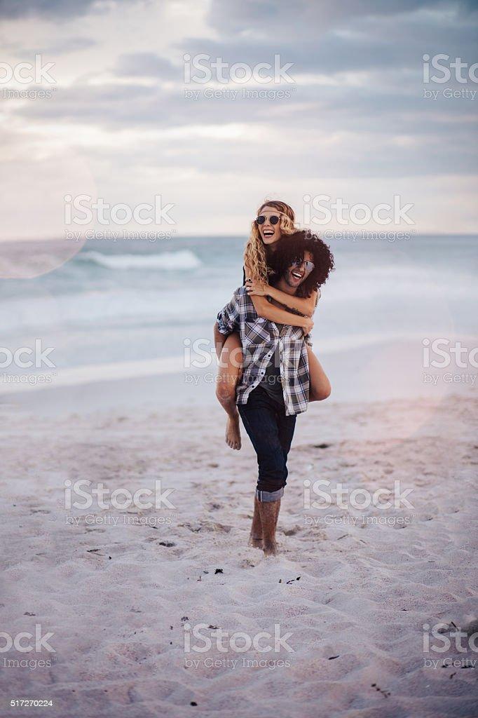 Boho Girl Rides Piggyback on hipster Man at Beach stock photo