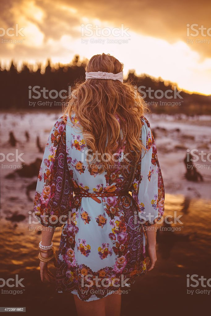 Boho girl walking in nature at sunset stock photo