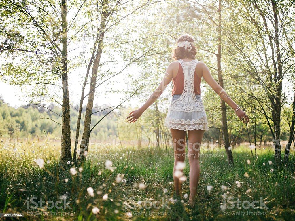 Boho girl walking through summer park feeling free stock photo