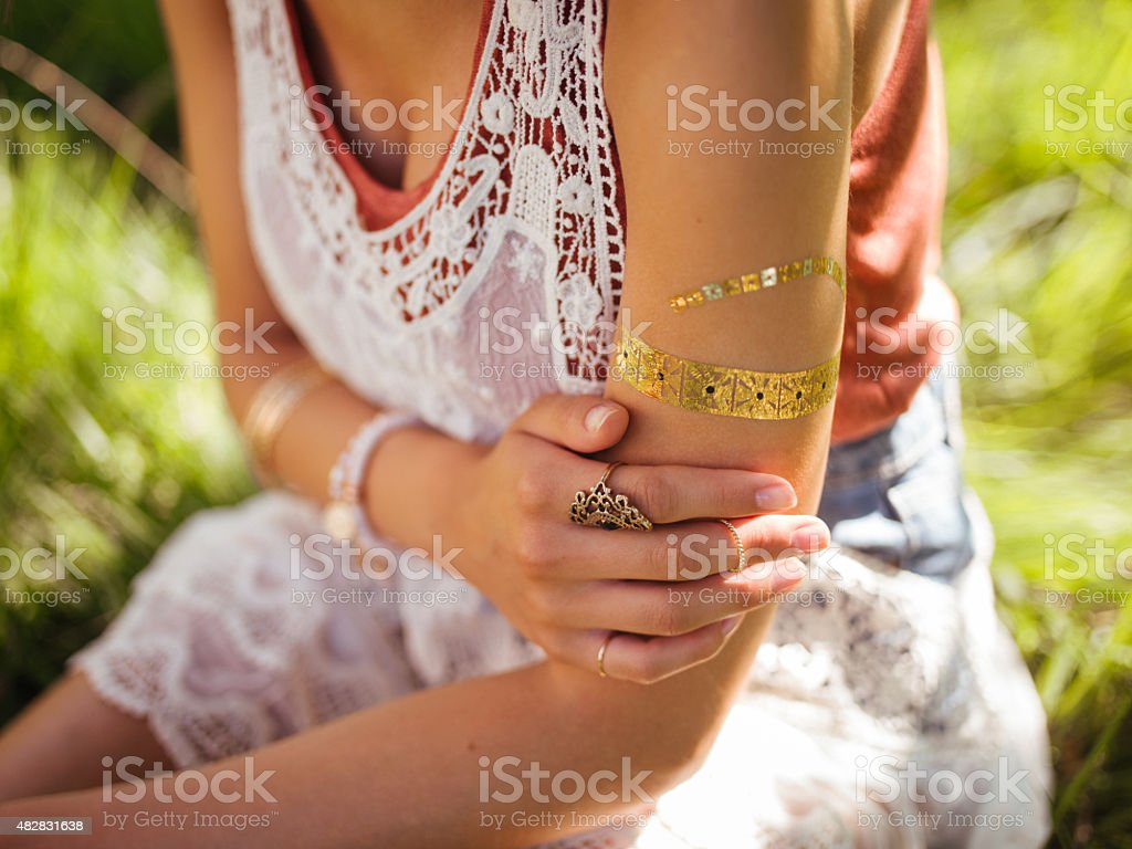 Boho girl with a gold foil temporary arm tattoo stock photo