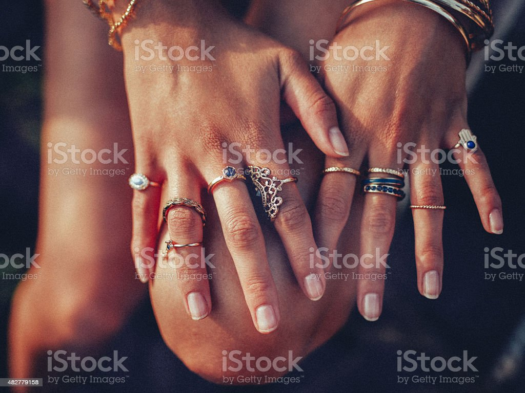 Boho girl's hands looking feminine with many rings stock photo