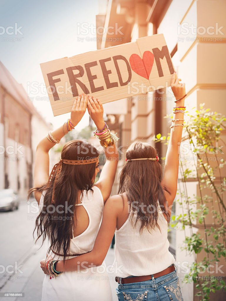 Boho girls holding carton board with text 'Freedom' stock photo
