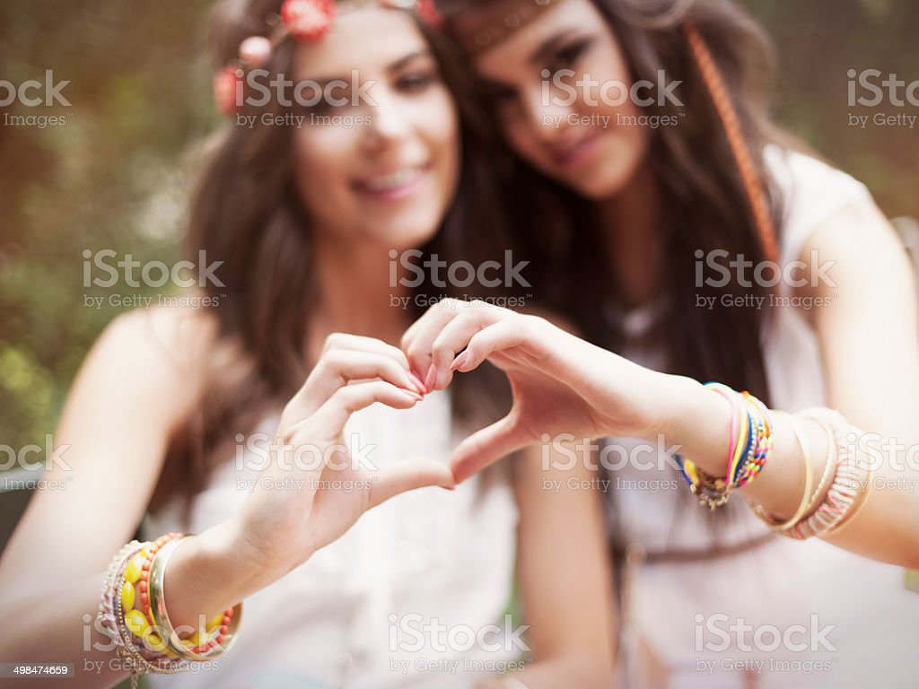 Boho girls showing heart shape from hands stock photo