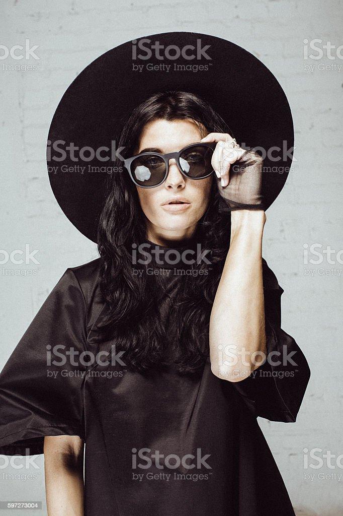 Boho style woman in studio staying near brick wall stock photo