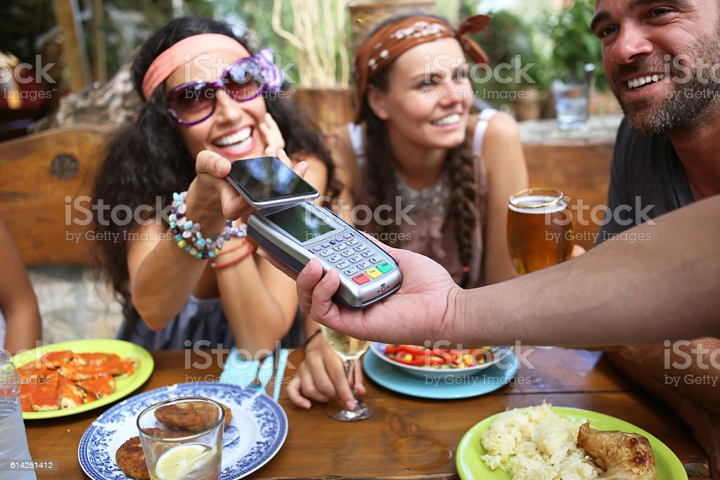 Boho woman using smart phone for mobile payment in restaurant stock photo