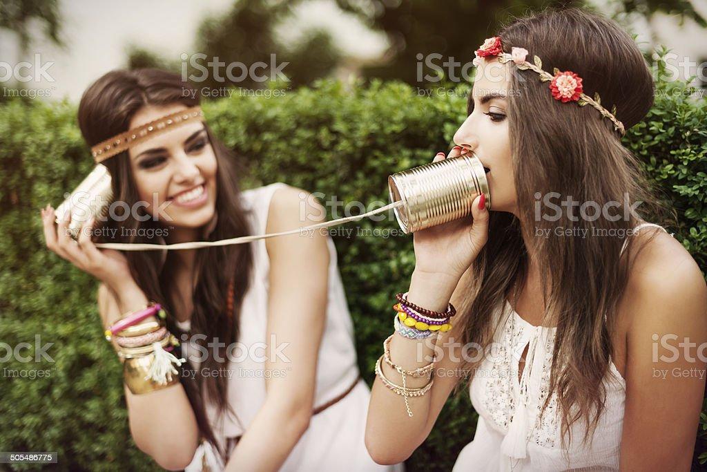 Boho women talking by tin can phone stock photo