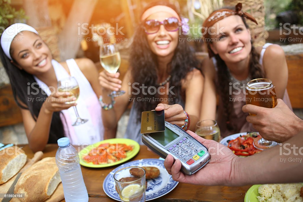 Boho women using credit card for contactless payment in restaurant stock photo