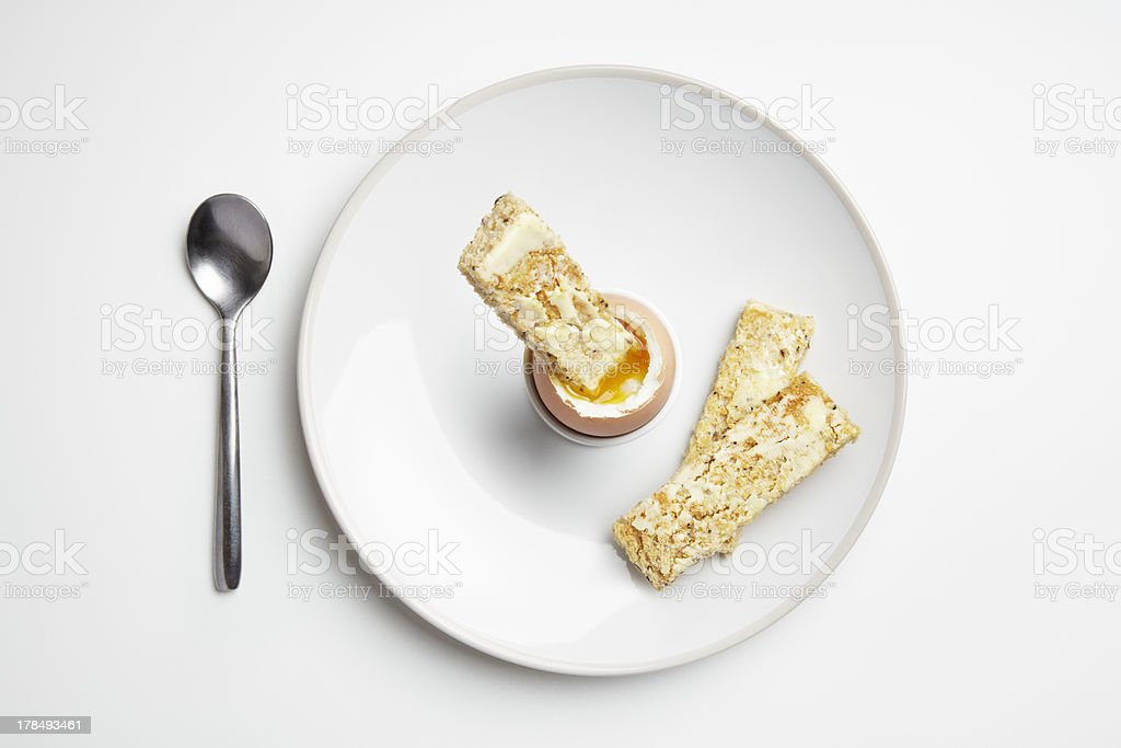 Boiled egg and toast soldiers on plate with spoon royalty-free stock photo