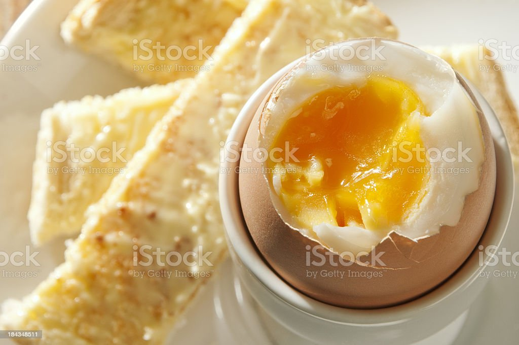 Boiled egg in eggcup overhead with buttered toast soldiers stock photo