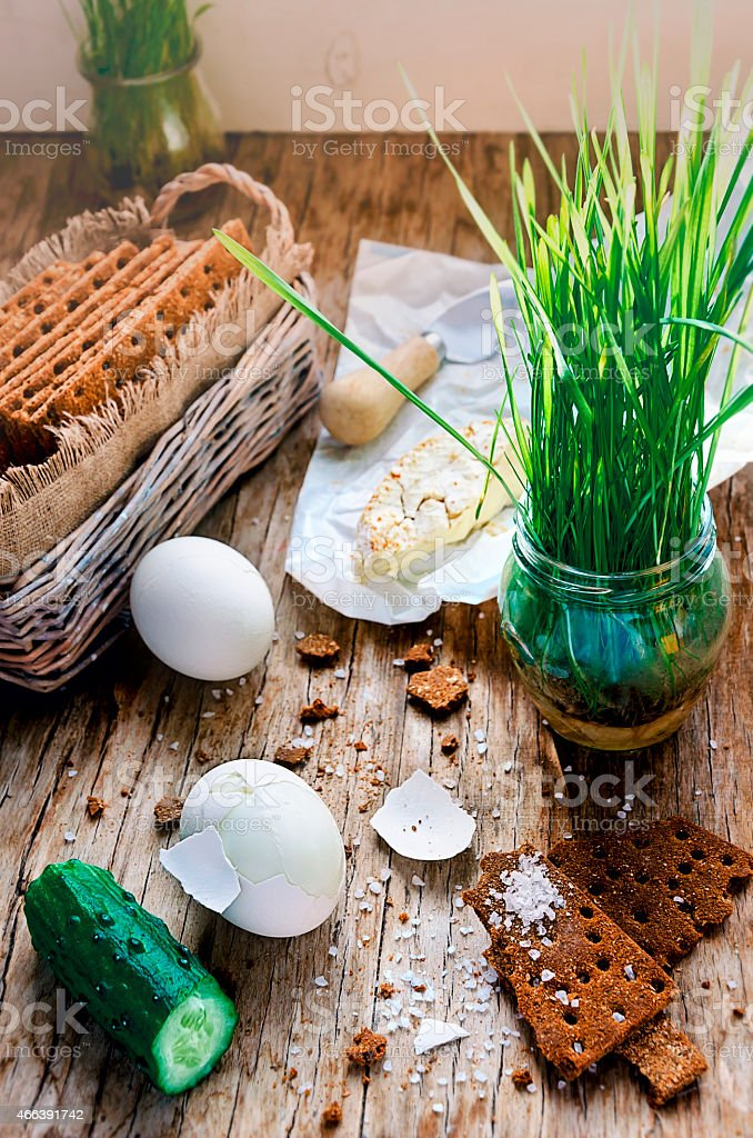 Boiled eggs, crispbreads, halved cucumber, camembert and young growth stock photo