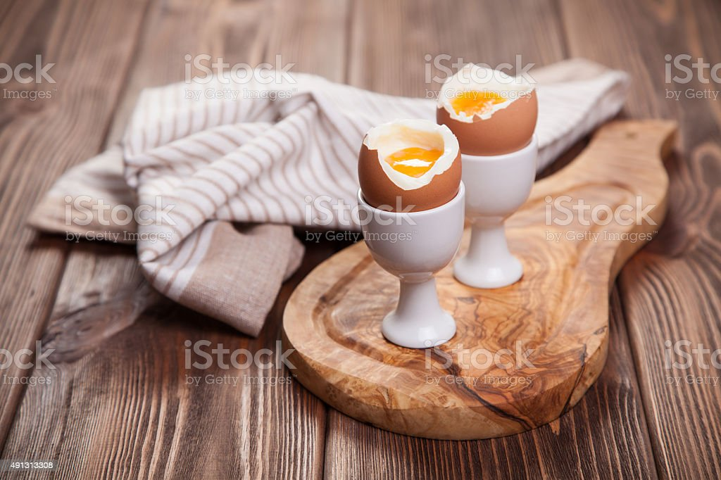 Boiled eggs on a wooden background stock photo