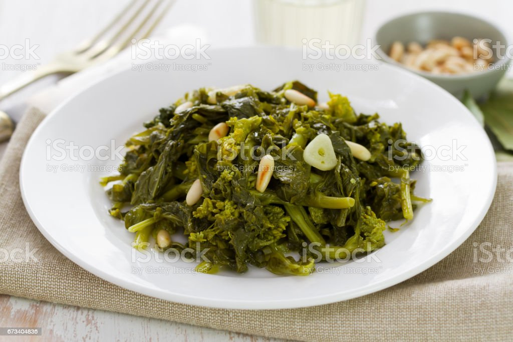 boiled greens with nuts and garlic on white plate on white wooden background stock photo