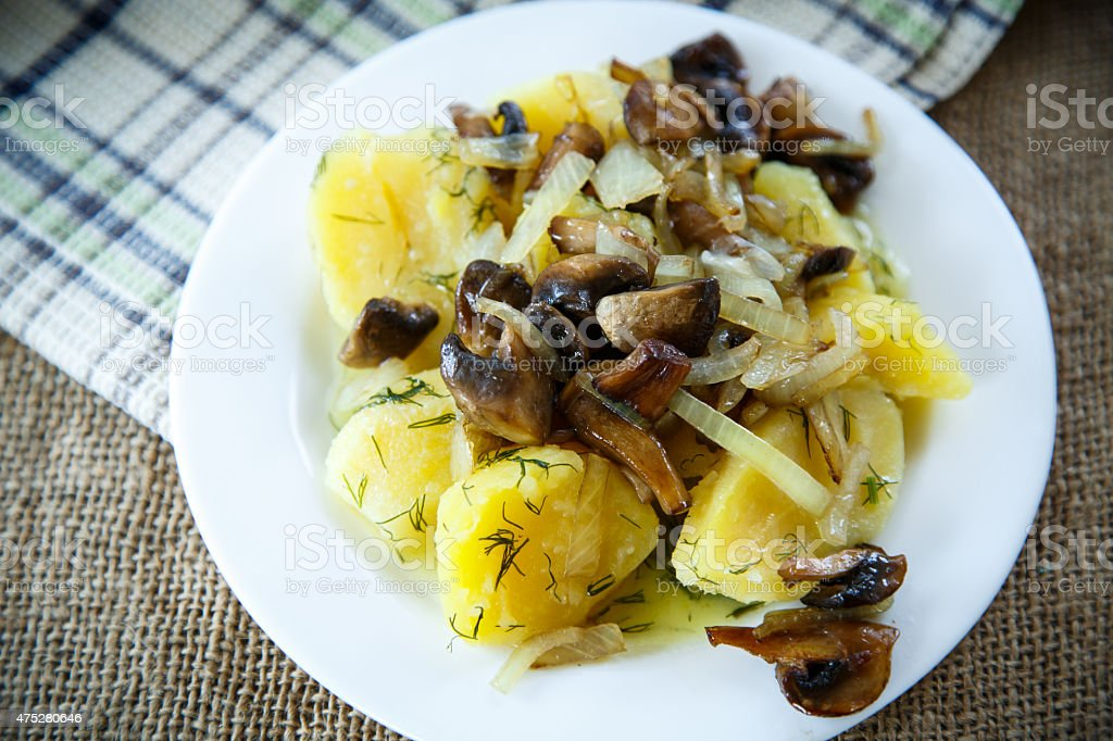 Boiled potatoes with fried mushrooms stock photo