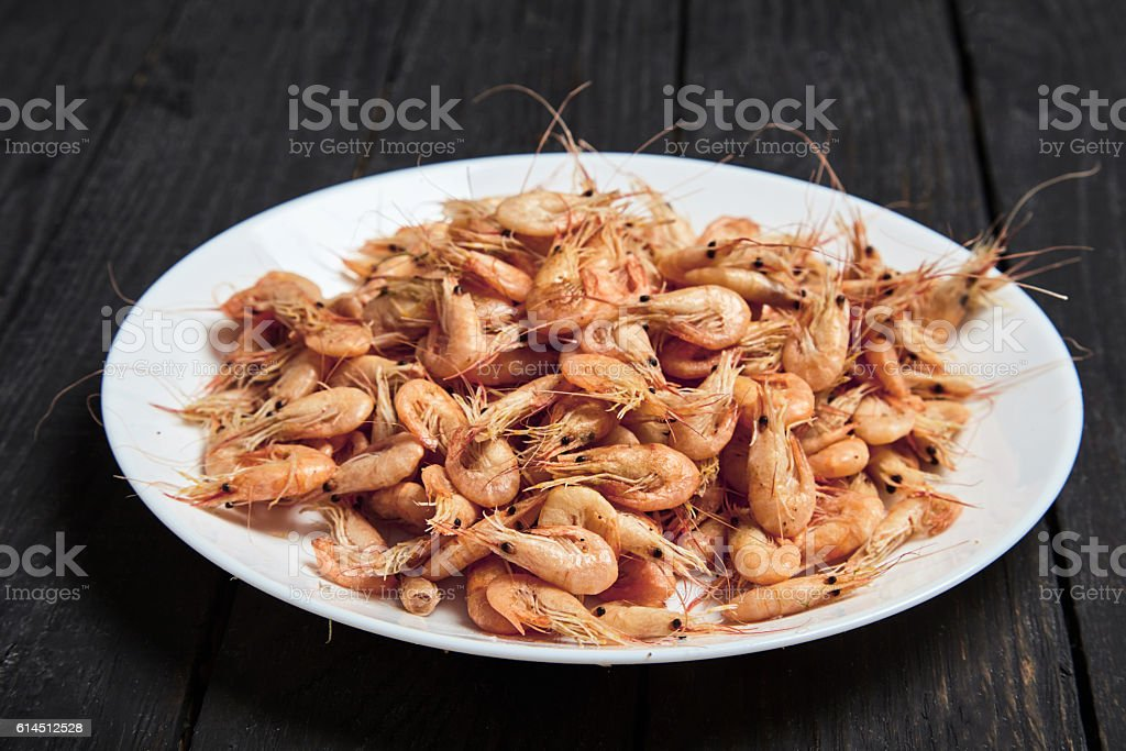 Boiled shrimp in shell with salt on white plate stock photo