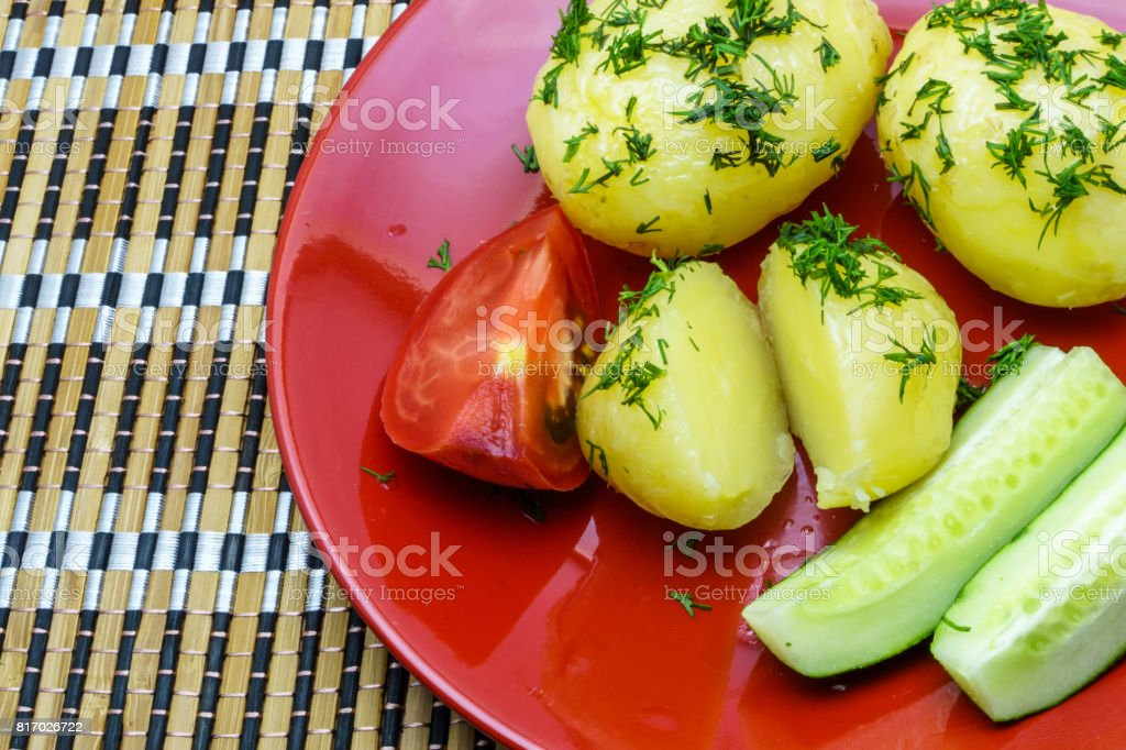 Boiled young potatoes with slices of cucumber and tomato on a plate stock photo