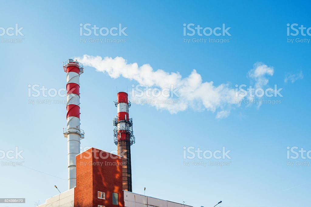Boiler house chimney. Steam against the clear blue sky. stock photo