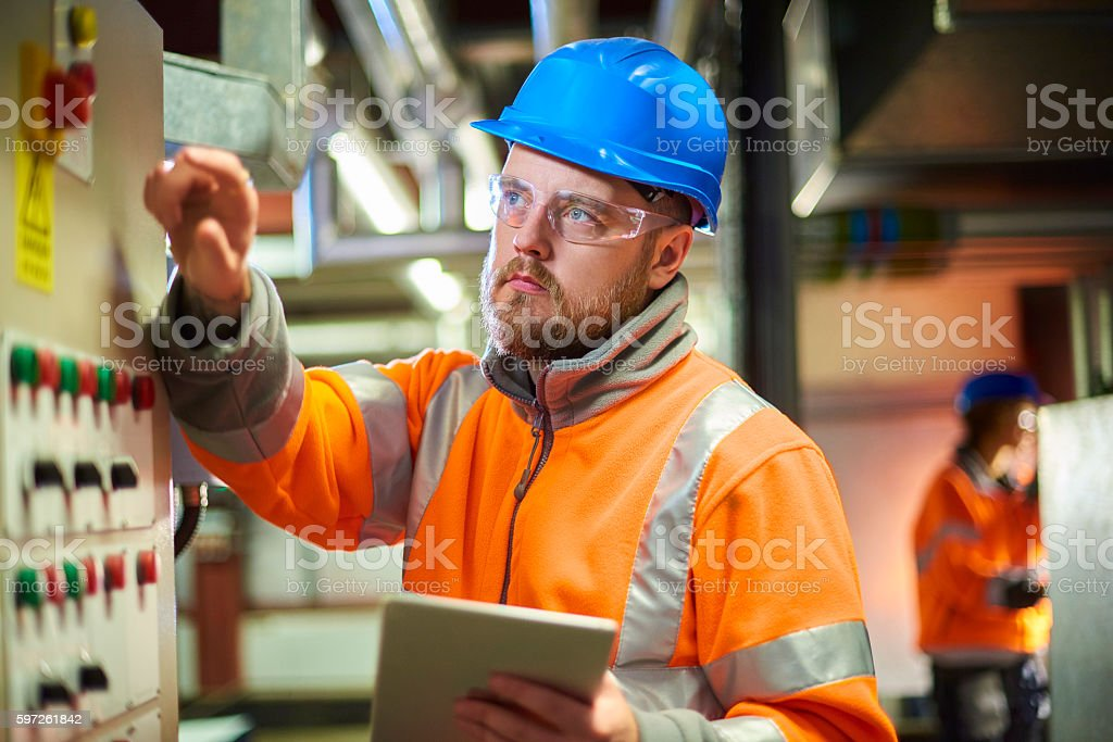 An industrial service engineer conducts a safety check of a control...