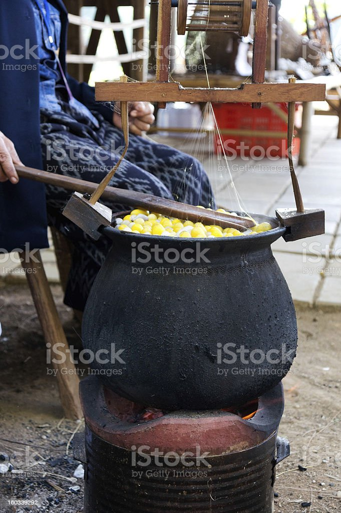 Boiling cocoon in a pot to prepare silk. royalty-free stock photo