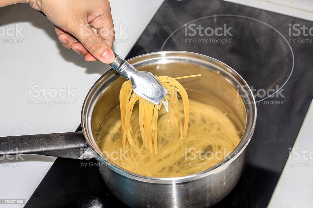 boiling spaghetti noodles in the pot stock photo