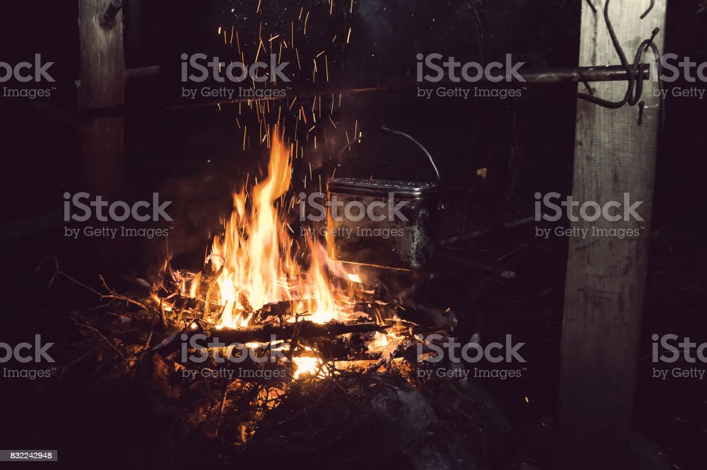Boiling water in the bowler on the bonfire. stock photo