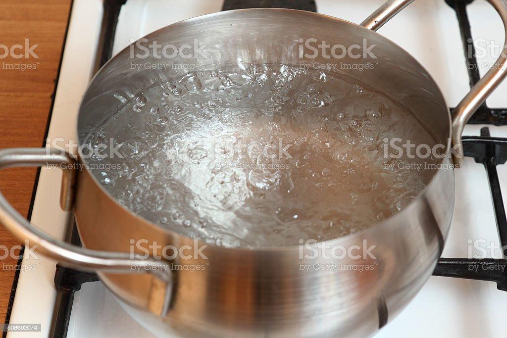 Boiling water into saucepan stock photo