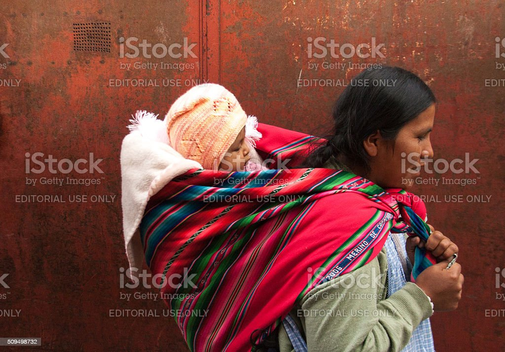 Bolivia: Quechua Woman with Baby on Back, Red Background (Close-Up) stock photo