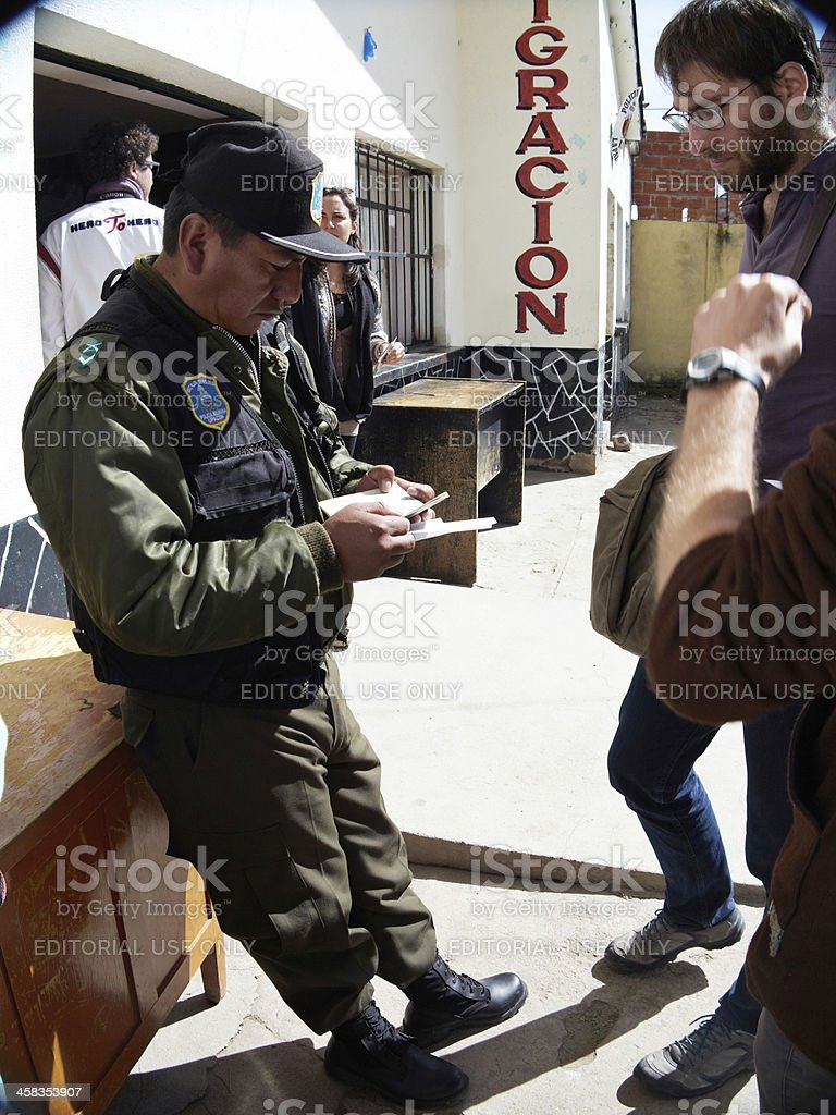 Bolivian border control guard checking passports stock photo