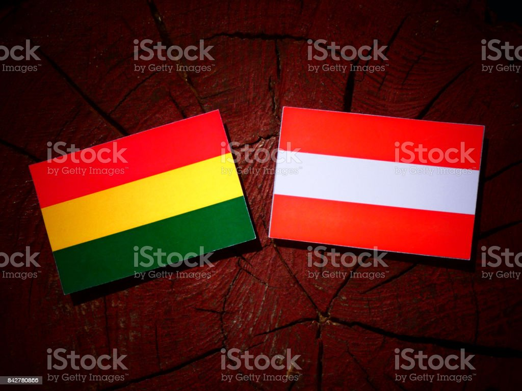 Bolivian flag with Austrian flag on a tree stump isolated stock photo
