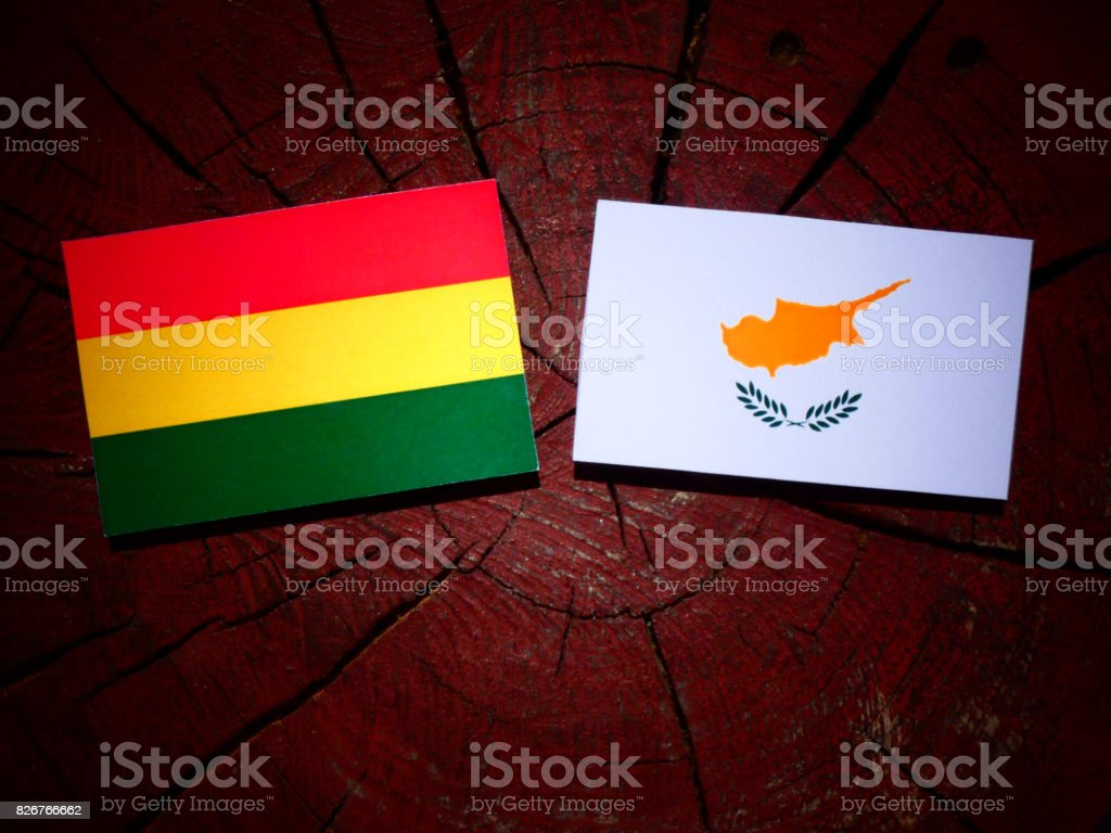Bolivian flag with Cypriot flag on a tree stump isolated stock photo