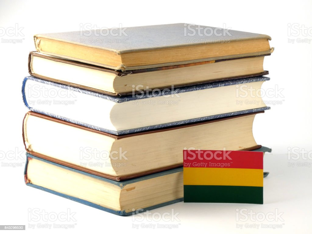 Bolivian flag with pile of books isolated on white background stock photo