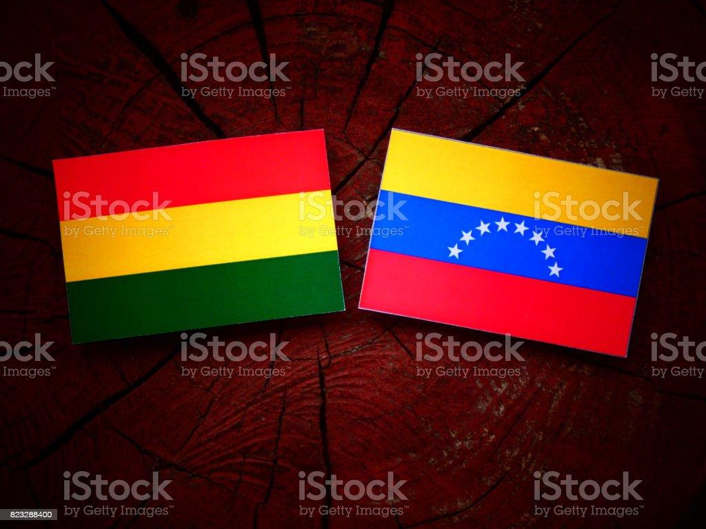 Bolivian flag with Venezuelan flag on a tree stump isolated stock photo