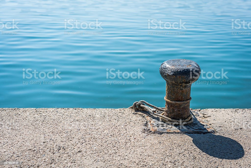 Bollard, rope and a sea. stock photo