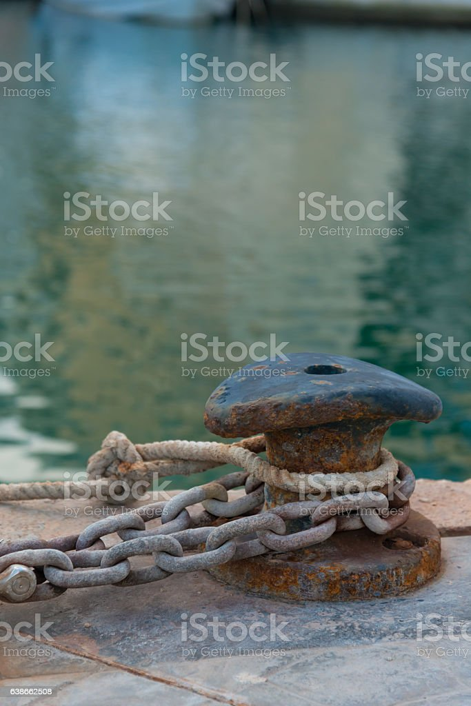 bollard with anchor chain in harbor - shadow of ship stock photo