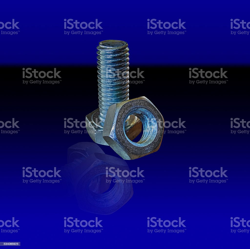bolt and nut on a dark blue background royalty-free stock photo