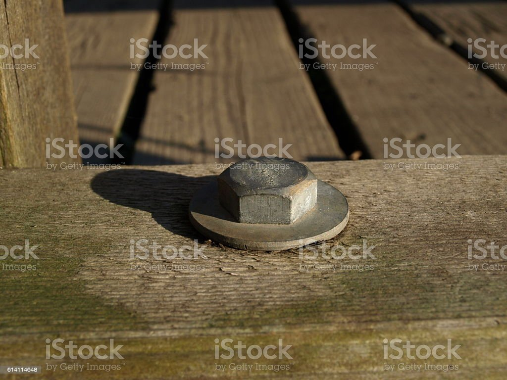 Bolt and washer on wooden boardwalk stock photo