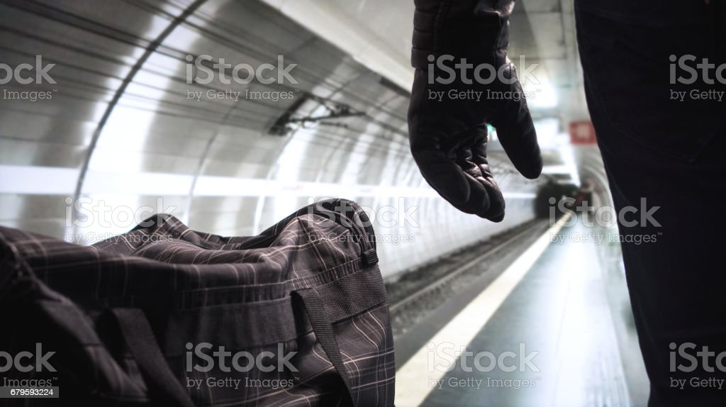 Bomber standing next to his black bomb bag planning a strike. Terrorist in underground subway tunnel looking at the empty metro platform. Security threat in public transportation. Terrorism concept. stock photo