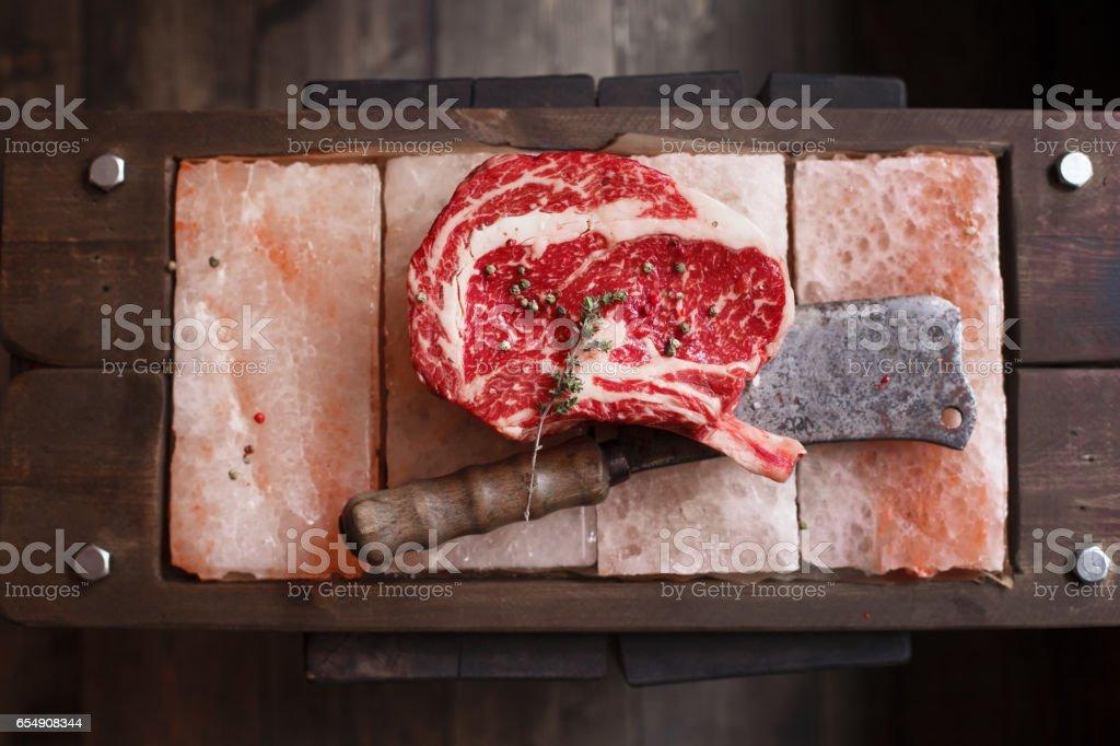 Bone In Rib Eye row Steak on pieces of salt stock photo