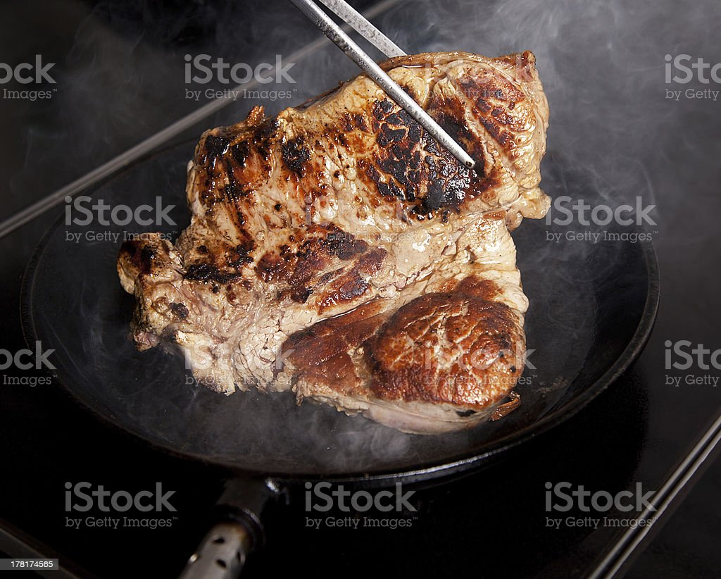 bone steak caught by a clamp in the pan closeup royalty-free stock photo