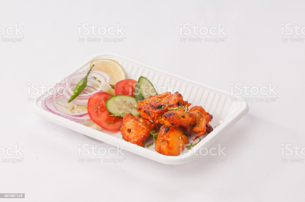 Boneless chicken tikka with mint dip and fresh salad stock photo
