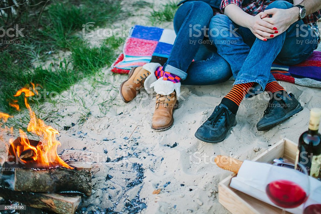 Bonfire on beach and couple sitting on background. Shallow focus. stock photo