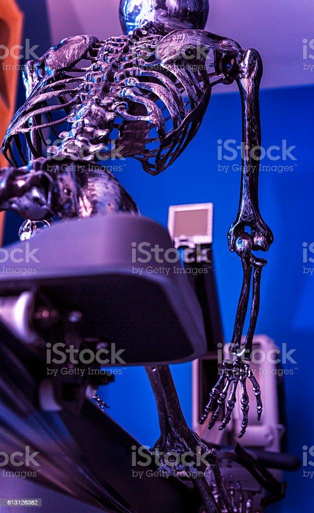 Bony Rib Cage Halloween Skeleton Athlete Exercising On Stationary Rower stock photo