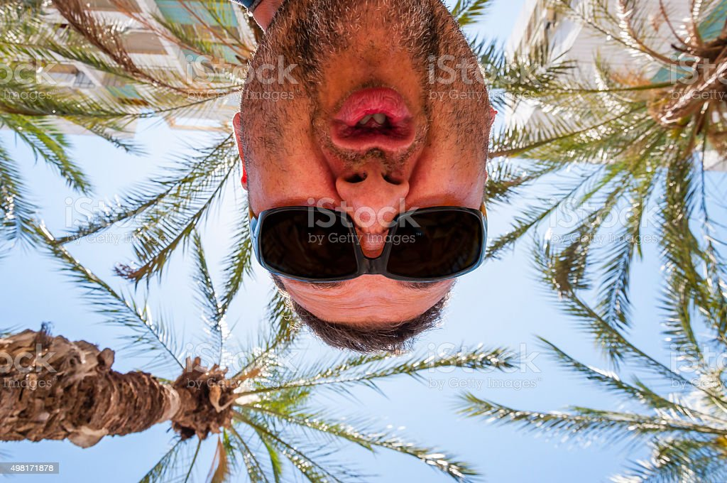 Booh! Scary grimace of unshaven man with sunglasses from above stock photo