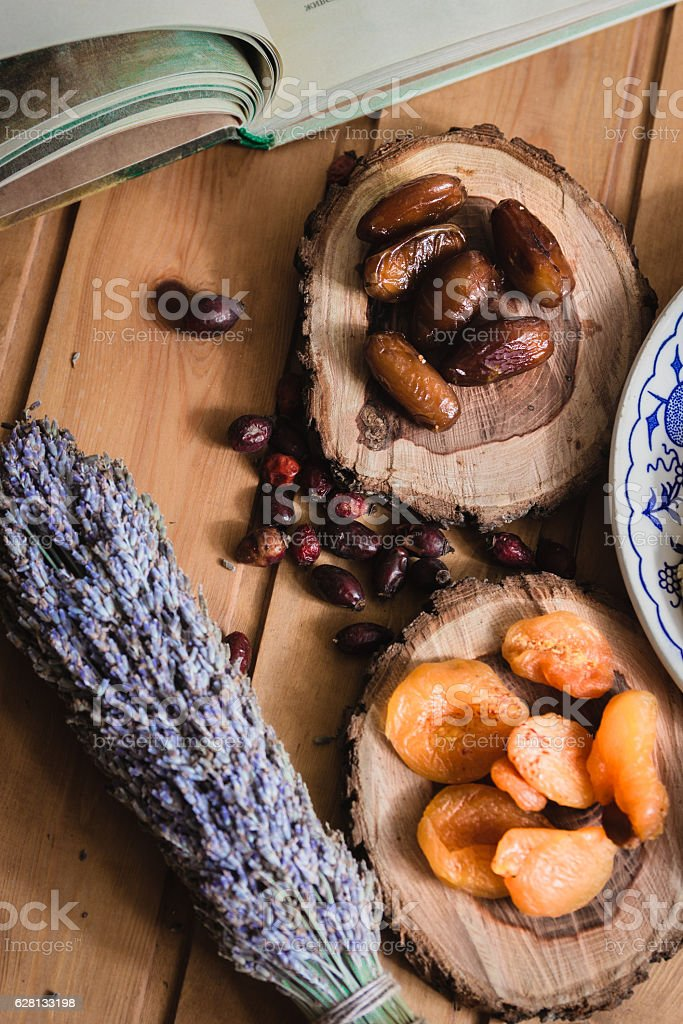 book and dried fruits on wooden plates stock photo