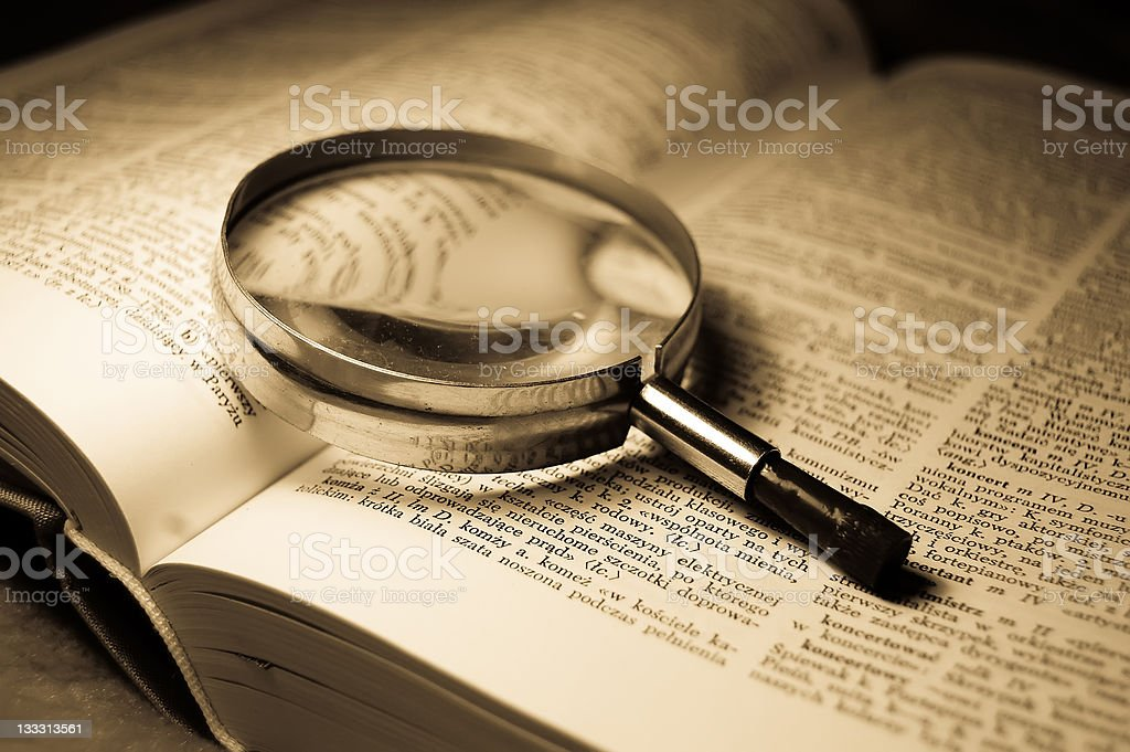 Book and glass loupe stock photo