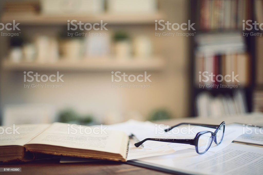 book and glasses on a table in home interior stock photo
