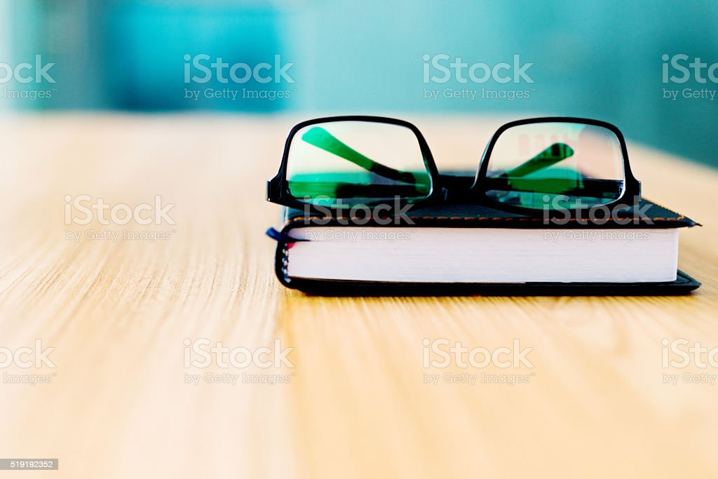 Book and glasses on desk stock photo