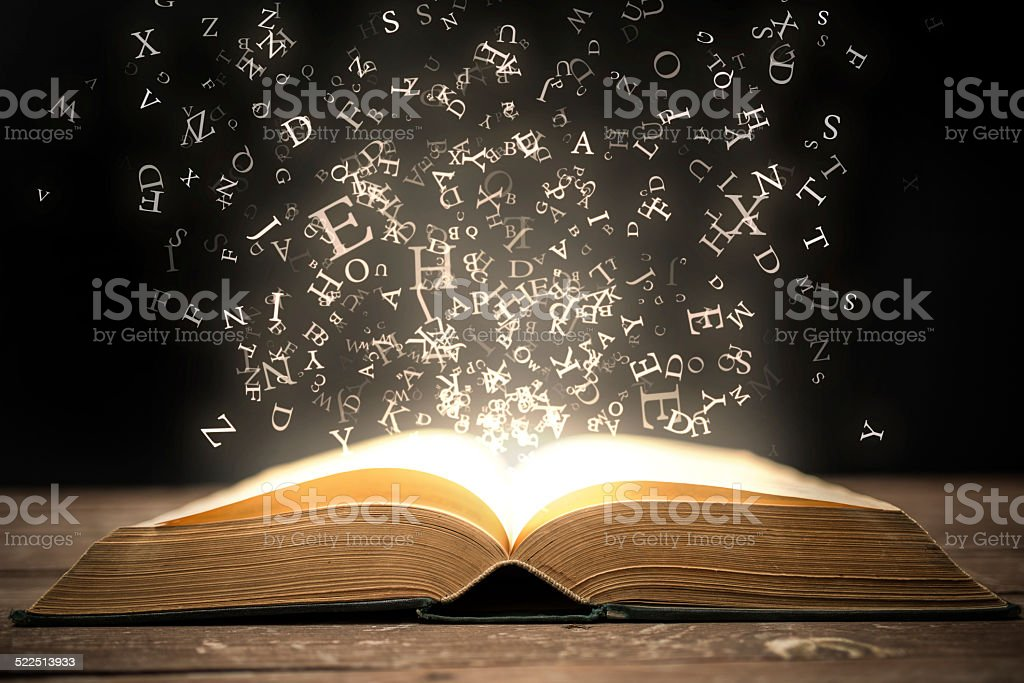 Book and glowing letters stock photo